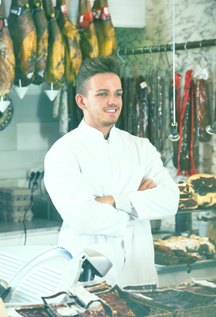 clothing store: calm young seller working at butcher market Stock Photo