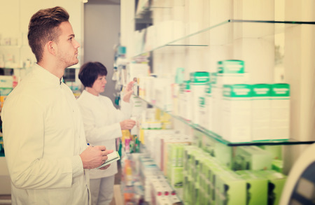 clothing store: Portrait of two laughing adult pharmacists working in modern farmacy