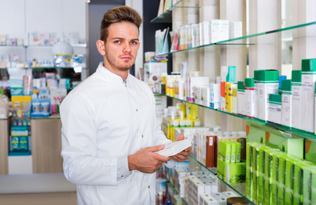 Smiling male pharmacist wearing white coat standing among shelves in drug store Stock Photo