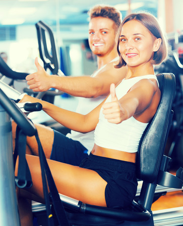 Happy woman spinning bicycle on weight loss training in gym
