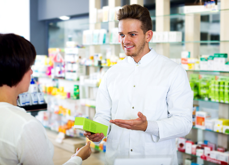 Handsome adult man druggist in white coat giving advice to customers in pharmacy