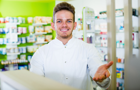 Laughing man pharmacist wearing white coat standing among shelves in drug store Stock Photo