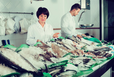 store shelf: Ordinary fish and seafood store with two happy adult sellers indoors Stock Photo