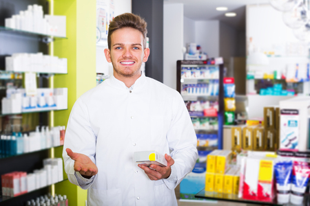 Happy young pharmacist wearing uniform and working in pharmaceutical shop Stock Photo