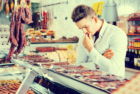 clothing store: Stylish dark-haired buyer thinking and comparing different types of raw meat Stock Photo