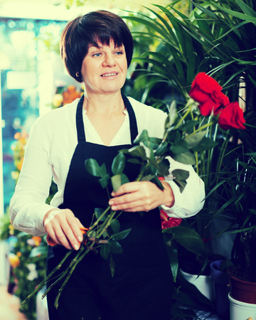 Smiling shop assistant displaying bright red roses in flower shop