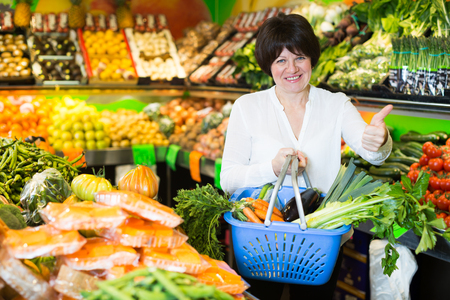 Middle aged woman with basket choosing vegetables on the market