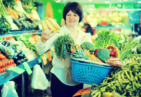 Adult female taking fruits and vegetables with basket on the market
