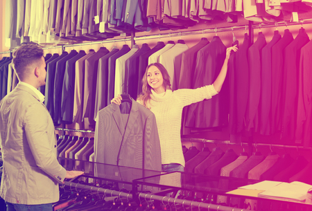 clothing store: female seller demonstrating shirts to customer in men's cloths store