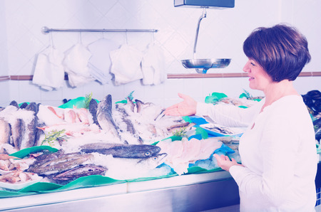 Mature client choosing fish in store and smiling Stock Photo