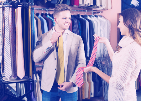 clothing store: Young positive couple deciding on tie in men�s clothes store Stock Photo