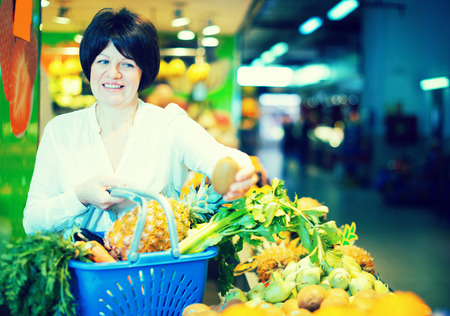 Middle aged woman with basket choosing fruits on the market