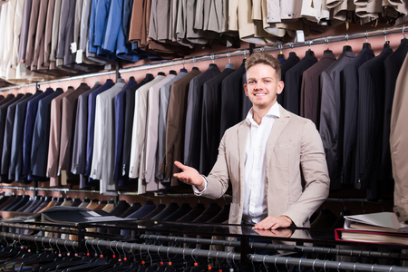 happy male shopping assistant offering various suits in men�s cloths store