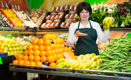 Mature woman offering fresh vegetables and fruits on the market Stock Photo