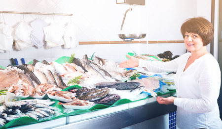 Woman choosing fish in store and smiling Stock Photo