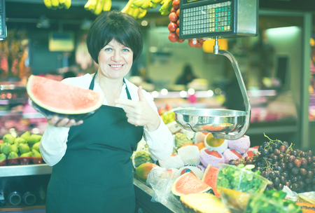 Adult female selling watermelon and other fruits on the market