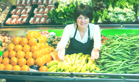 ensaladilla rusa: Portrait of adult female selling fruits and vegetables on the store