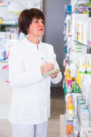 clothing store: smiling positive  woman pharmacist wearing uniform and working in pharmaceutical shop