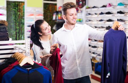 sleeveless hoodie: Happy loving couple deciding on new sportswear in sports store