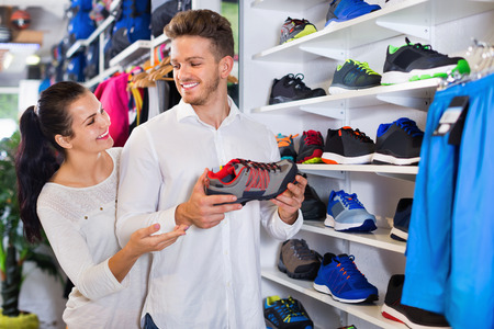 comprando zapatos: Young cheerful  couple choosing new sneakers in sports store
