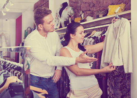 clothing store: Two young customers selecting jacket in clothing shop. Focus on both persons Stock Photo