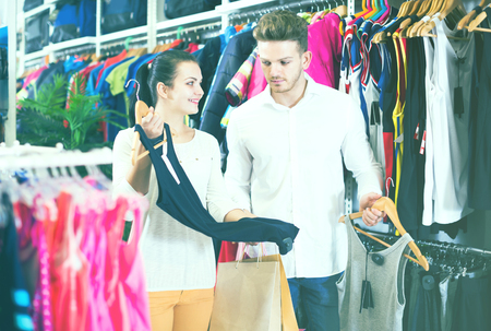 sleeveless hoodie: Glad couple deciding on new sportswear in sports store Stock Photo