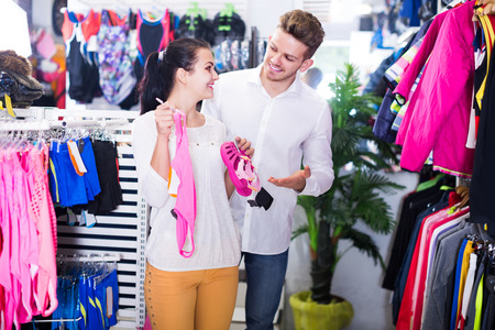 Young american loving couple deciding on children's swimwear in sports store
