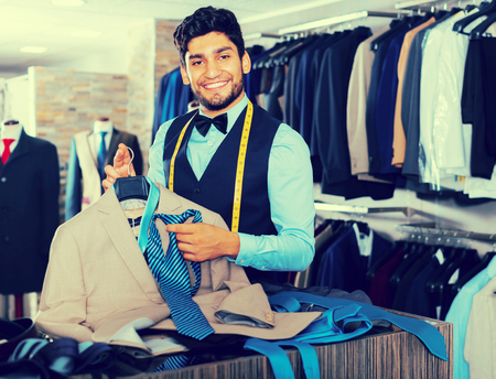 Young male designer is creating business image in mens clothes shop Stock Photo