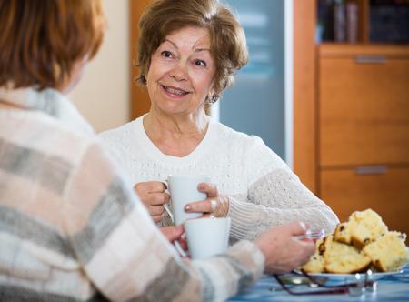お茶を飲むと、笑いながら肯定的な女性の年金者の肖像画
