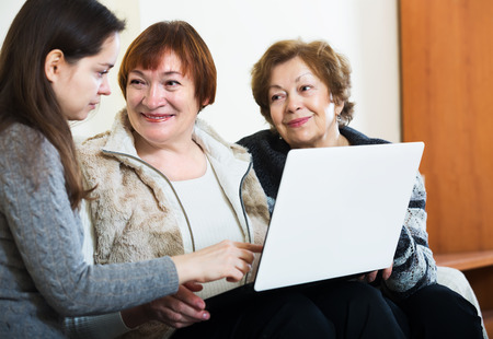 Aged women and young girl with laptop at home Banco de Imagens