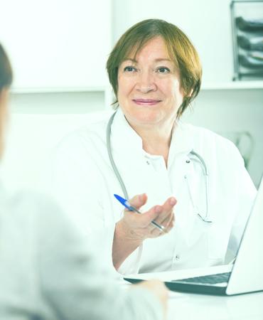 Mujer joven que tiene consulta con el médico femenino en el hospital