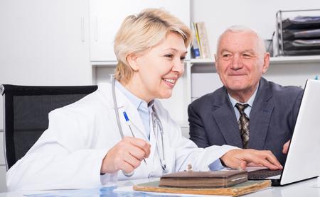 cliente maduro visitar la consulta de sexo masculino con la mujer médico en el hospital