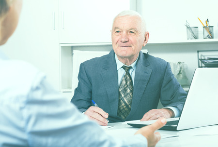 Senior male manager having meeting with client in his office