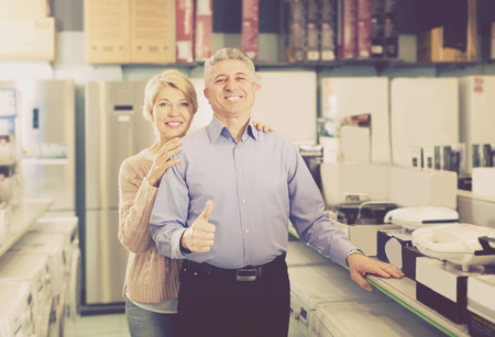 appliances: Smiling mature couple in home appliance shop to discuss items for the kitchen and home