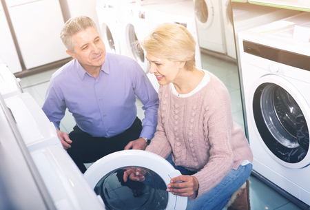 mature couple chooses washing machine for their house in shop of household appliances refrigerator for your house