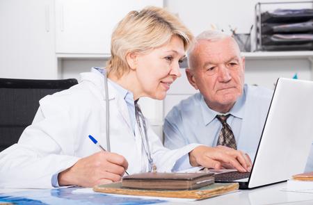 Senior hombre teniendo consulta con doctora en el hospital