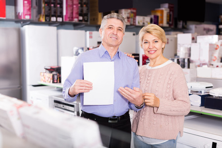 appliances: Charming mature couple took credit for home appliances in center of household appliances