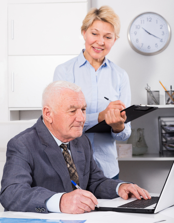 Aged manager and secretary working productively together in office Stock Photo