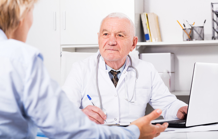 Mature female client having consultation with man doctor in hospital