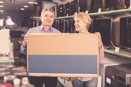 appliances: middle-aged married couple in shop packed household appliances into boxes for transportation to themselves home