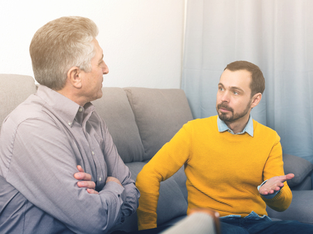 Adult father and son discuss family problems at home on couch