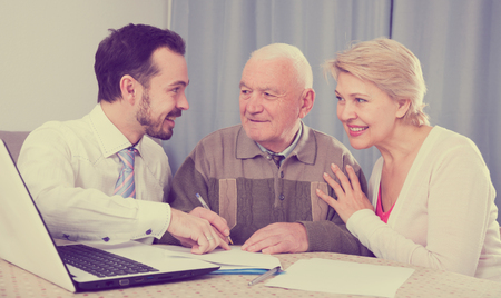 accounts payable: Smiling mature woman and old man studying conditions of contract with manager at home