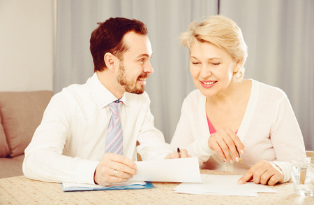 Smiling mature female and sales manager sign contract at home Stock Photo