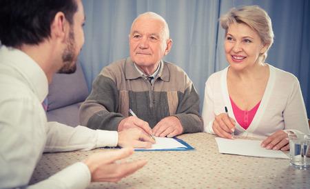 Anciano y mujer madura con el gerente del departamento social completan el cuestionario Foto de archivo