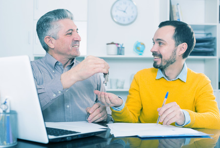 Mature man and young agent sign rental agreement in agency and hand over keys Stock Photo