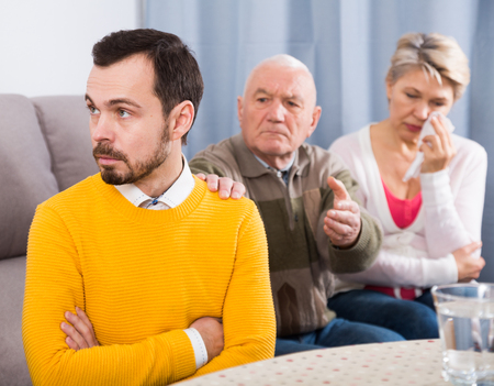 Elderly grandfather talking seriously and instructs his grandson at home Stock Photo
