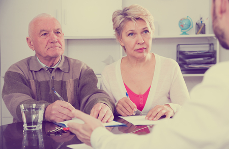 accounts payable: Mature woman and her elderly father signing credit agreement with smiling credit department employee Stock Photo