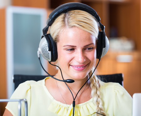Cheerful young woman with headset working at call-centre Stock Photo