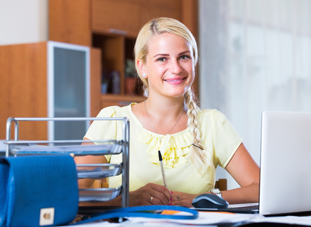 Smiling business woman with notebook and documents at work