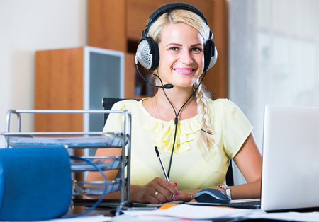 smiling american girl answering the call of technical support and smiling
